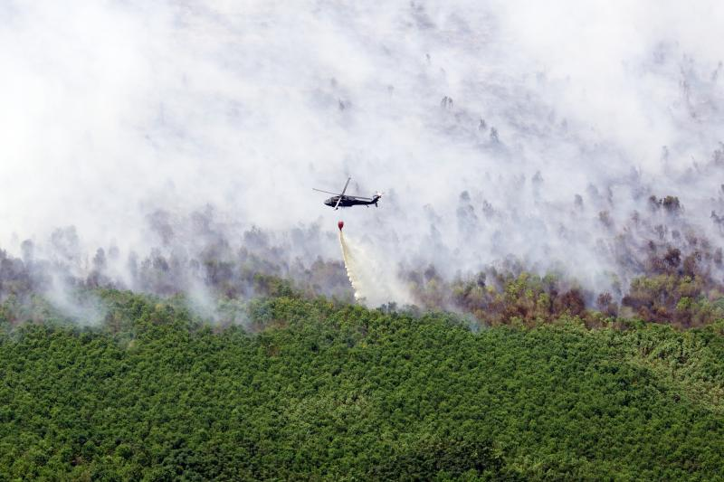 Louisiana National Guard Blackhawks douse marsh fire with 500-gallon water drops.