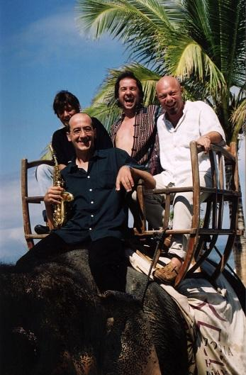Mezcal Jazz Unit riding an elephant on one of their trips around the world.
