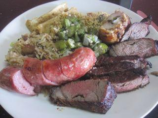 Steak, sausage and sides on a typical lunch plate at Churra's.