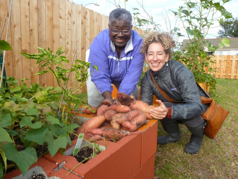 Linda Blunt and Abigail Feldman show off Linda's sweet potato harvest.
