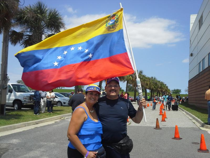 Ingrid and Fernando Yurdanet of Miami wave their Venezuelan flag at the voting center in Kenner.