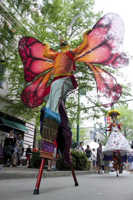 Stilt walkers from the Dragon Knights Stilt Theater delight the crowd on Jefferson Street Sunday.