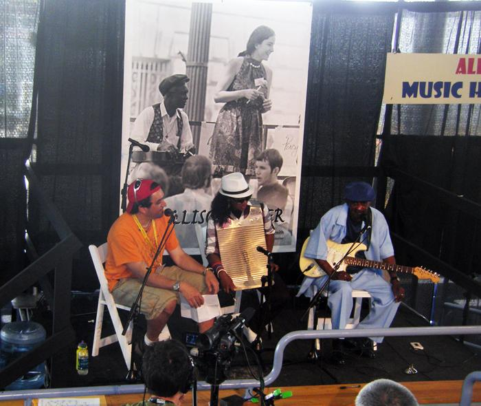 "David Kunian interviews Paul ""Lil' Buck Sinegal"" on the Allison Miner Music Heritage Stage. Sherelle Chenier, Cleveland Chenier's granddaughter, backs Lil Buck on washboard."