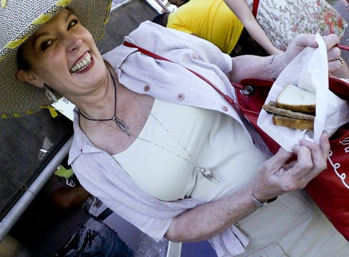 Our own Poppy Tooker at the Jazz Fest with a pork chop sandwich from Ms. Linda's Catering.