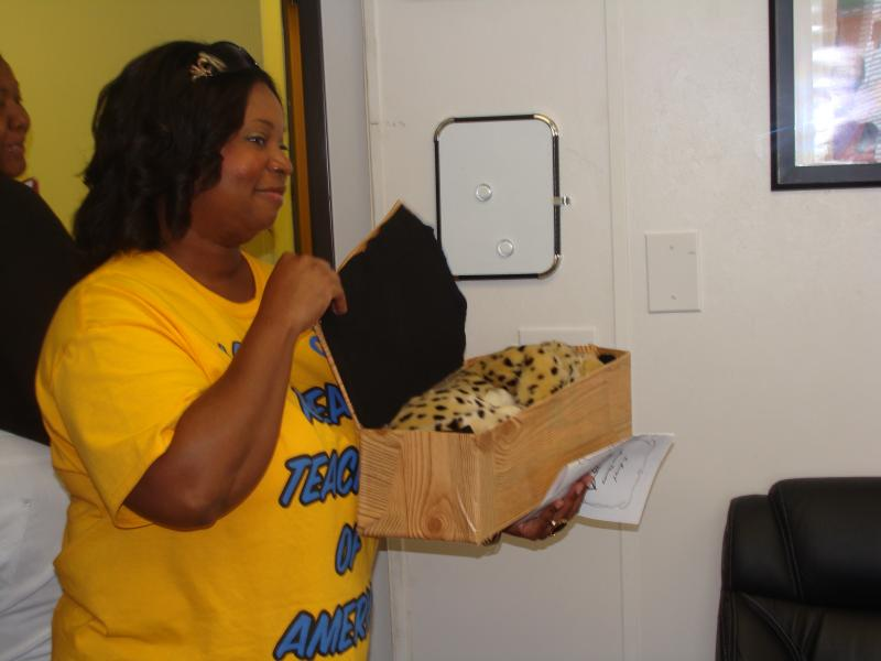 Tinya Thompson, instructional coach at Abramson, holds the Abramson wildcat in its coffin. The school has closed permanently, due to a geographic consolidation.