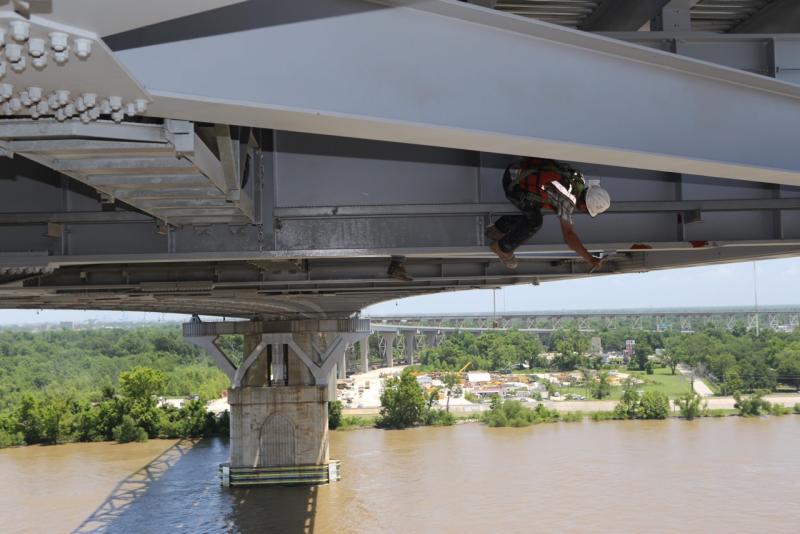 A worker paints the underside of the bridge.