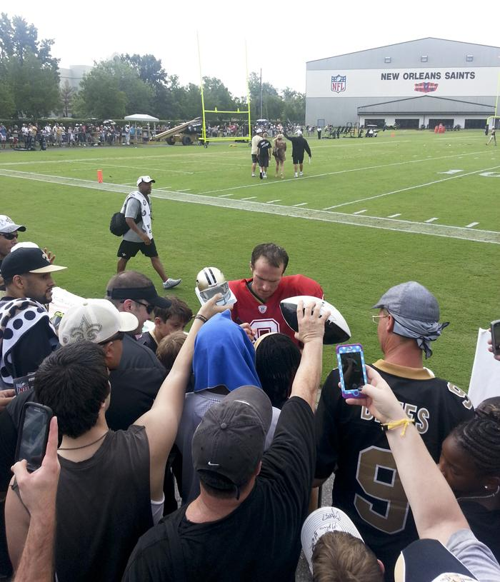 Quarterback Drew Brees signs autographs for fans.