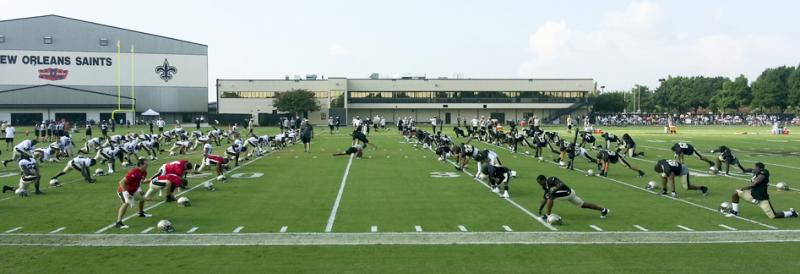 Saints players stretch it out on the field. Over 5100 fans turned out to see the annual Black and Gold Scrimmage.