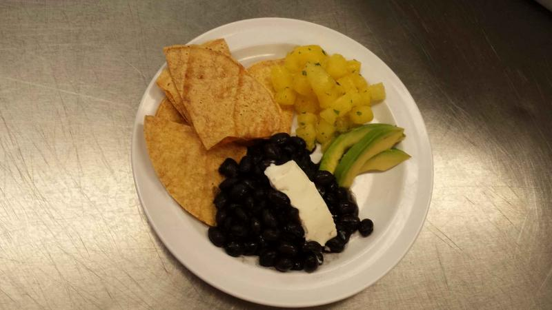 Black beans with baked corn tortilla chips, avocado, pineapple and cilantro salad, and yogurt cheese.