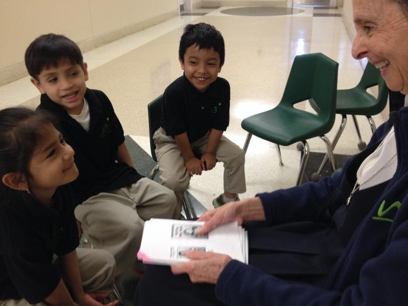 Sister Juanita Wood reads with a group of Spanish speaking kindergardeners.