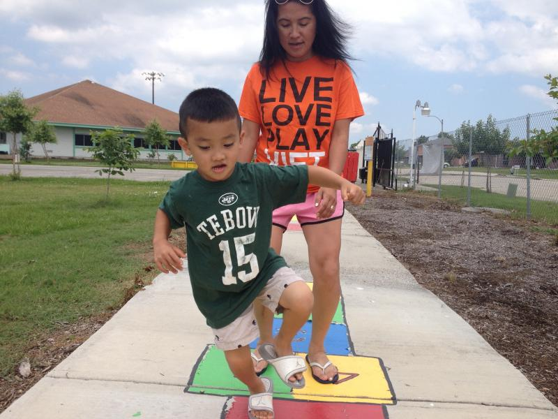 Sean plays hopscotch on the Born Learning Trail