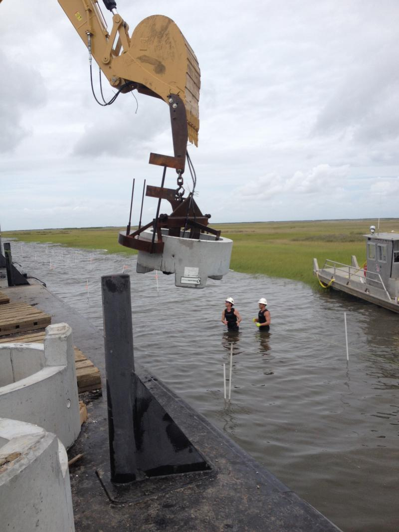 Concrete rings are lowered into the water off the Biloxi Marsh.