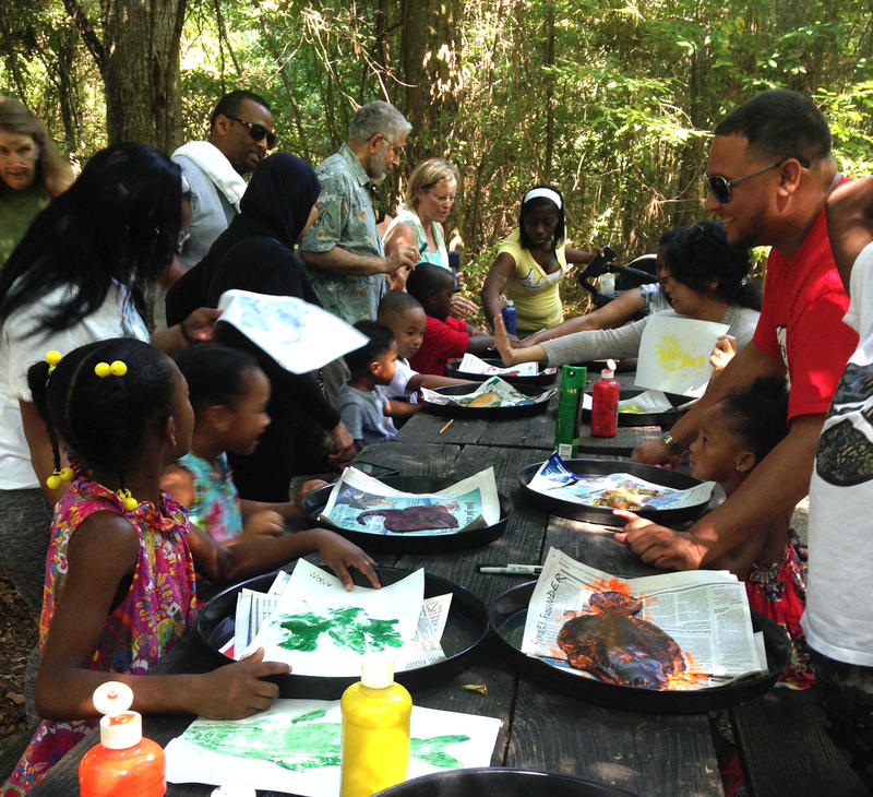 Volunteers help a group of children on a field trip make prints of local fish at the Northlake Nature Center.