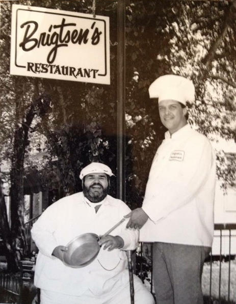 Chef Prudhomme and Chef Frank Brigtsen, passing the skillet outside of Brigtsen's Restaurant, 1986.