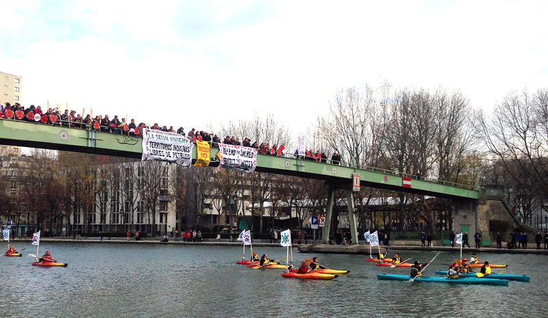 A group of indigenous people from all over the world led a kayak flotilla through a canal in central Paris.