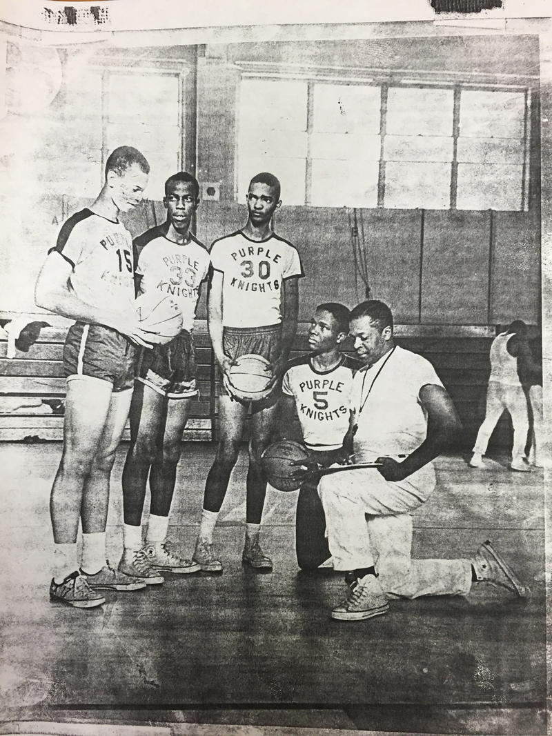 The Purple Knights pose on the court; Harold Sylvester is kneeling next to his coach.