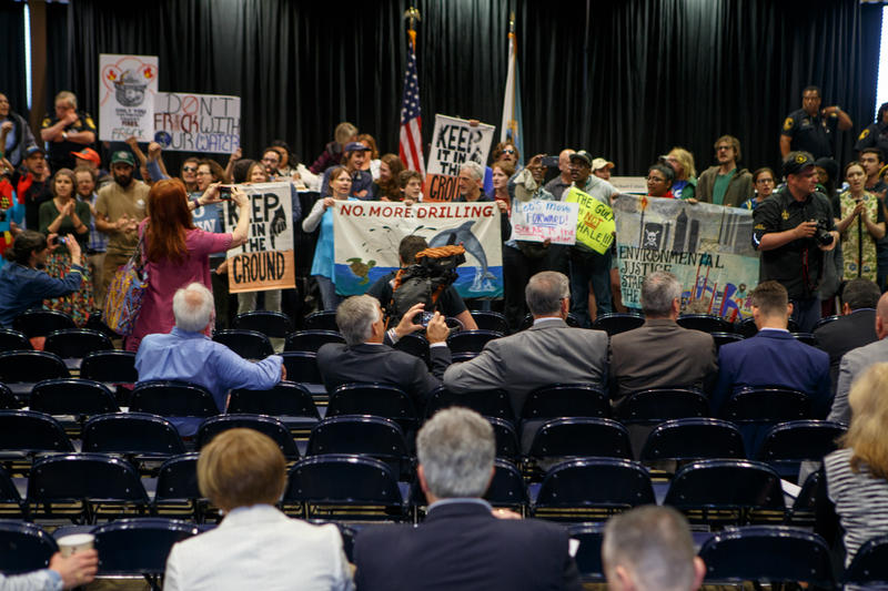 Businesspeople took photos as environmentalists interrupted the auction of offshore oil and gas leases at the Superdome Wednesday.