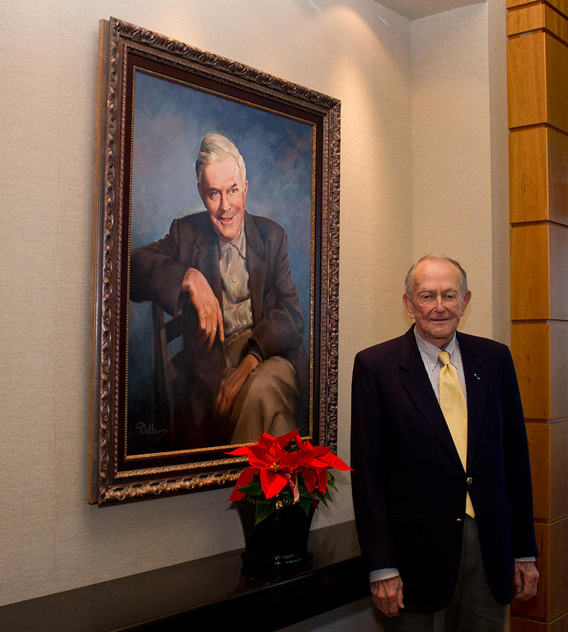 Paul Spencer stands beside a portrait of Joe W. Brown, the founder of the Brown Foundation.