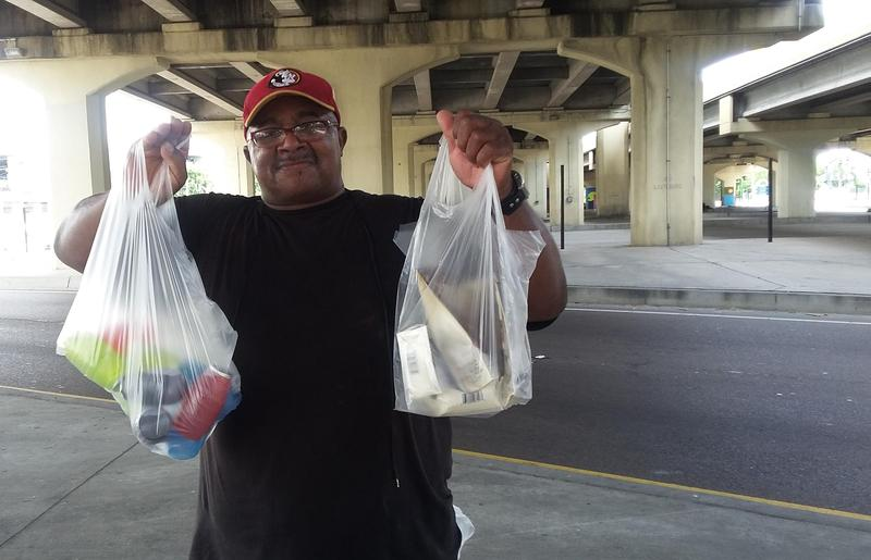Mission outreach coordinator Daniel Watts hands out snacks for homeless still living under the Pontchartrain Expressway recently cleared to make way for more downtown parking.