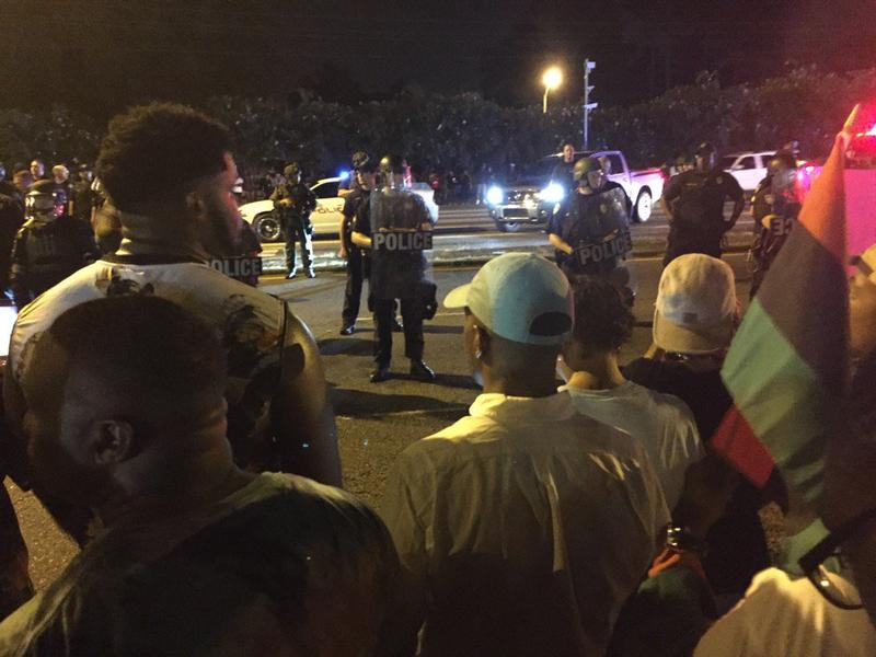 Baton Rouge police in riot gear face off with protesters Saturday night. Earlier in the evening WWNO reporter Ryan Kailath was arrested while covering the protest.