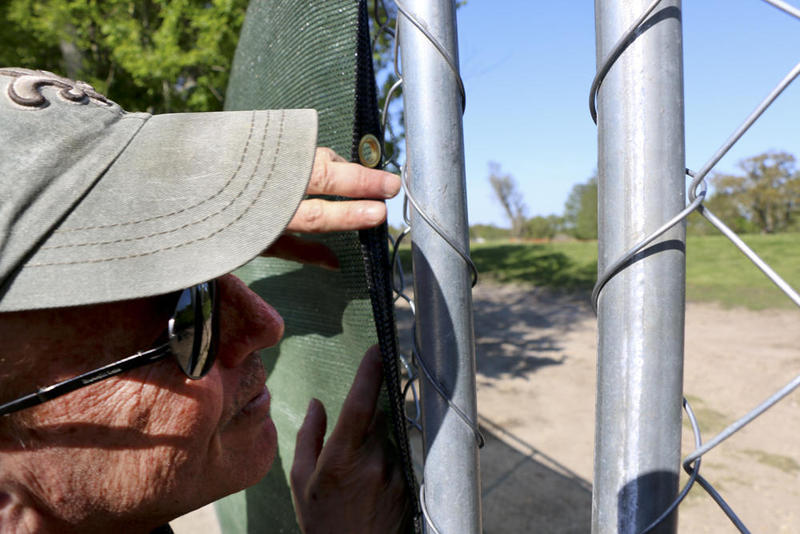 Jeff Katz, a member of the City Park For Everyone Coalition protest group, looks through a chain link fence. In the distance are police vehicles gathered near a man occupying a tree.