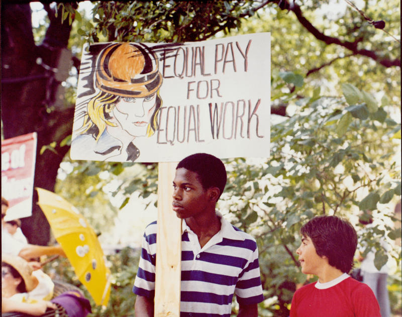 Boy holding an Equal Pay for Equal Work sign, ERA March and Jazz Funeral, 1982