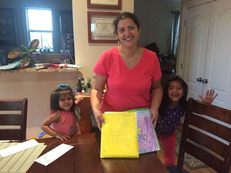Ingrid Thomas shows off her children's homework and communications folders. Back in December, their principal sent home a letter saying she'd like Ben Franklin Elementary to become a charter school.