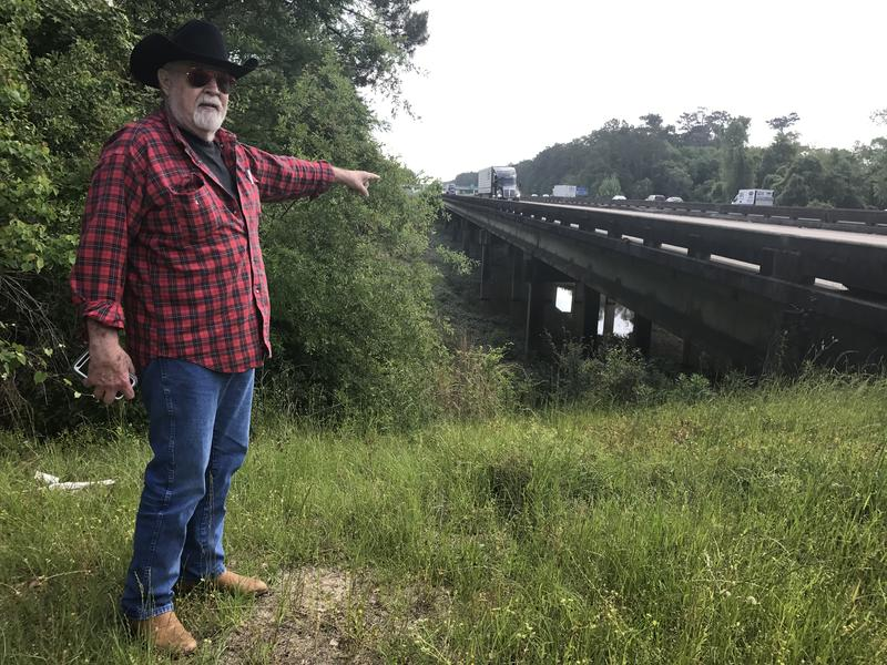 "Byard ""Peck"" Edwards points to one of three openings constructed in Interstate 12 that allows water to access the Tangipahoa flood plain."