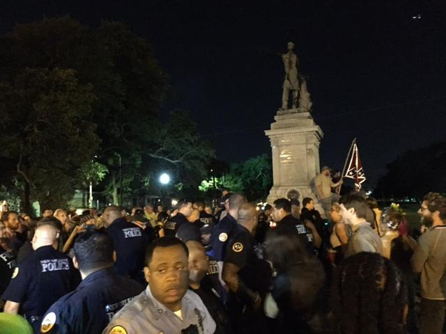 Police lined up from the monument to the road to allow confederate flag bearing protestors to safely exit site.