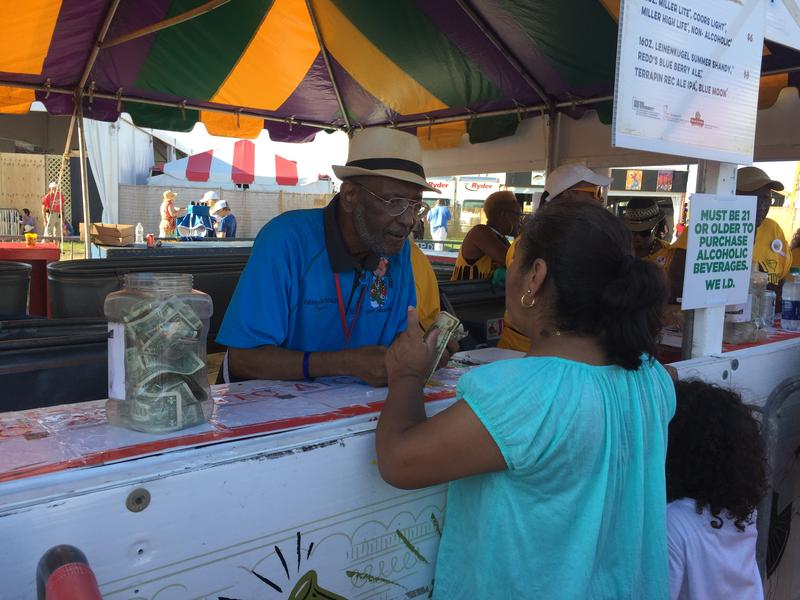 Johnny Jackson, Captain of the Zulu Diamond Cutters Krewe, works the beverage tent. The sales proceeds help defray Mardi Gras costs and support community events.