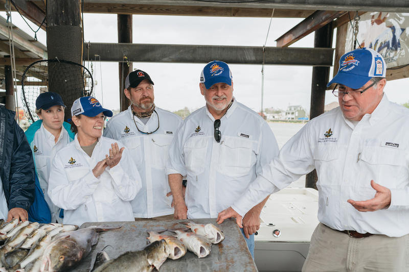 Poppy Tooker, chefs from the Dickie Brennan Restaurant Group and Dickie Brennan show off their catch of the day.