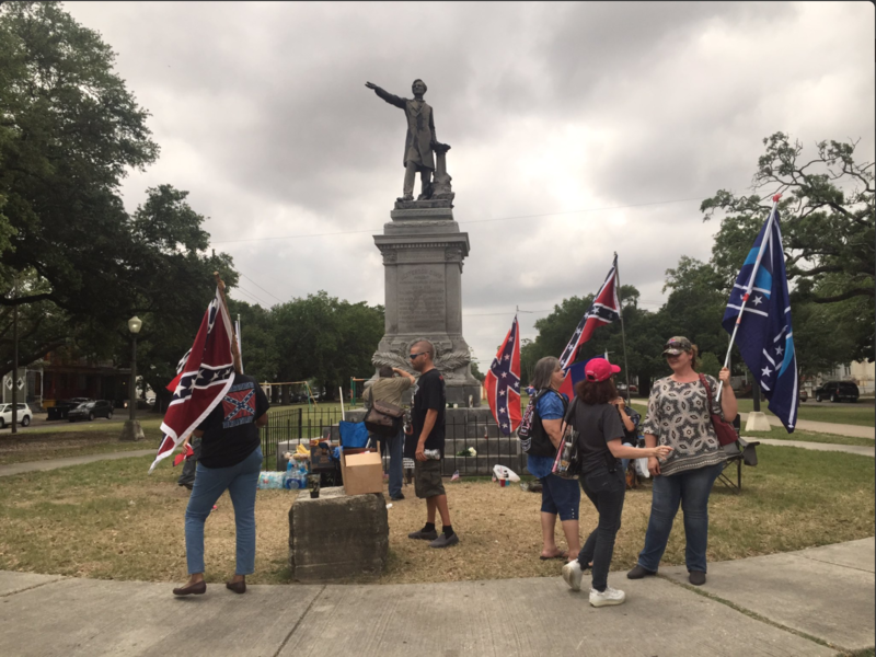 People protesting the removal of the confederate monuments guard the Jefferson Davis statue in Mid City.