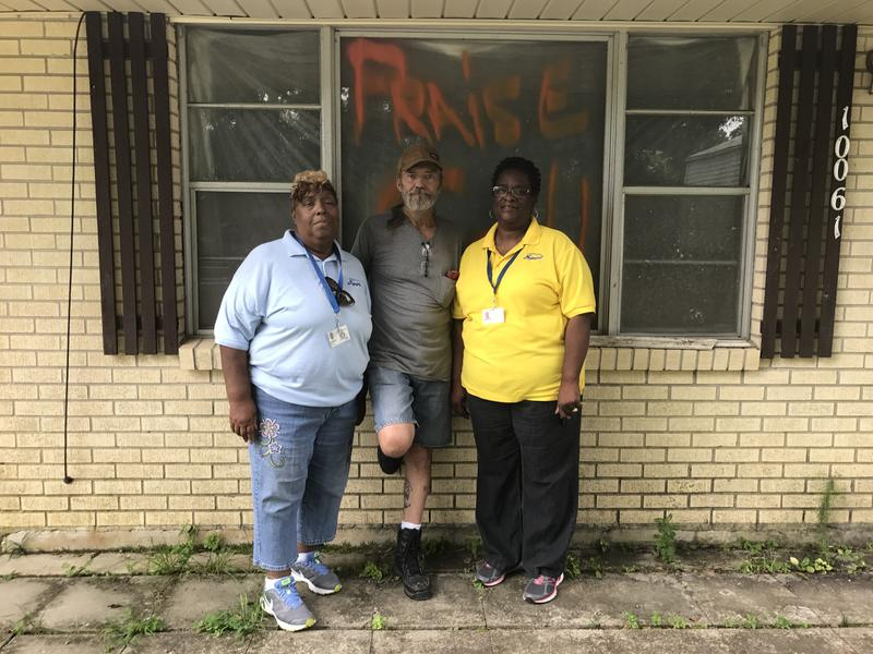 Flood victim James Farris stands with Edith Furlough (left) and Rosalie Willis (right) in front of his home in Central, La.