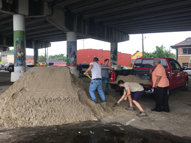 People bag sand underneath the Claiborne Expressway in preparation for the flooding that may occur over the next few days.