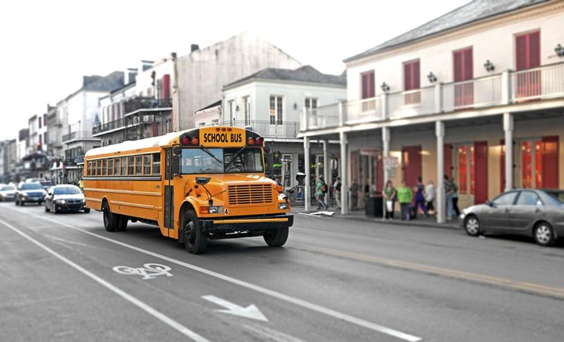 A bus travels up N. Rampart Street on its way to school.