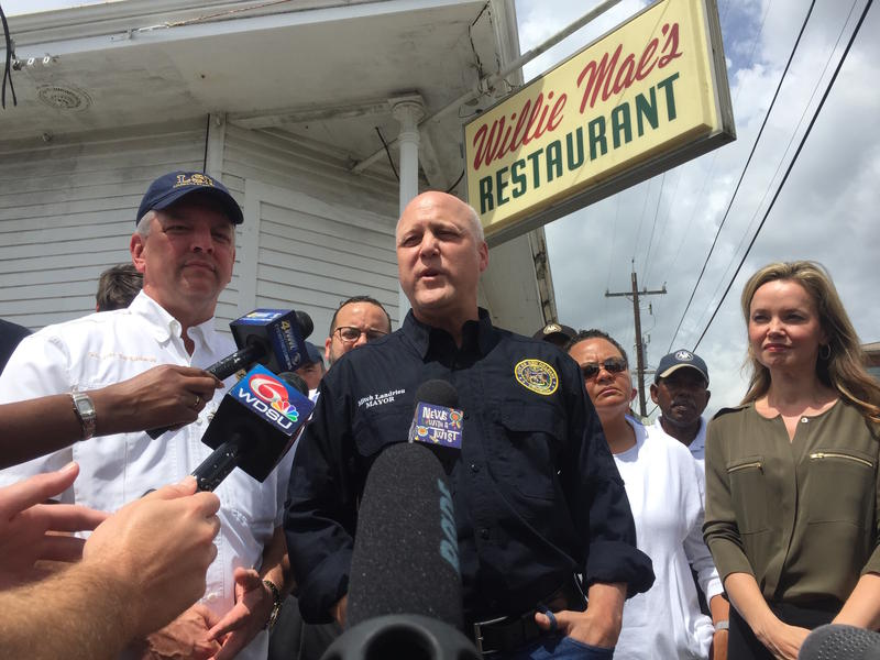 Gov. John Bel Edwards, left, and Mayor Mitch Landrieu, center, talk to members of the media outside of Willie Mae's Restaurant in the Treme neighborhood of New Orleans. The restaurant was one of several that flooded Saturday.