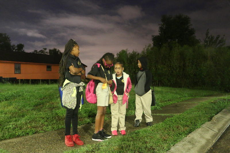 [From left to right] Cousins Tyjae Coston, Ri'yanna Hayes, Rh'niya Brown and Raynard Brown wait for their school bus on a corner in the Ninth Ward.