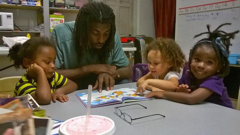 Derrick Strong reads to children at the Gentilly Community Center of Hope.