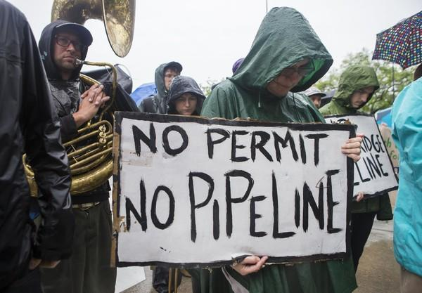 As the rain falls, protestors holds signs in opposition to the Bayou Bridge Pipeline in March of 2017.