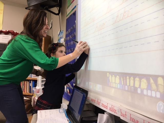 Cedarwood School teacher Niki Gazley helps one of her students, Regan King, practice writing in cursive.