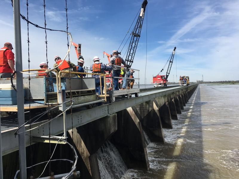 Army Corps of Engineers employees prepare to open the Bonnet Carré Spillway. The Spillway has 350 bays, each bay has 20 wooden beams that hold back the water. Workers will lift individual beams to open the Spillway.