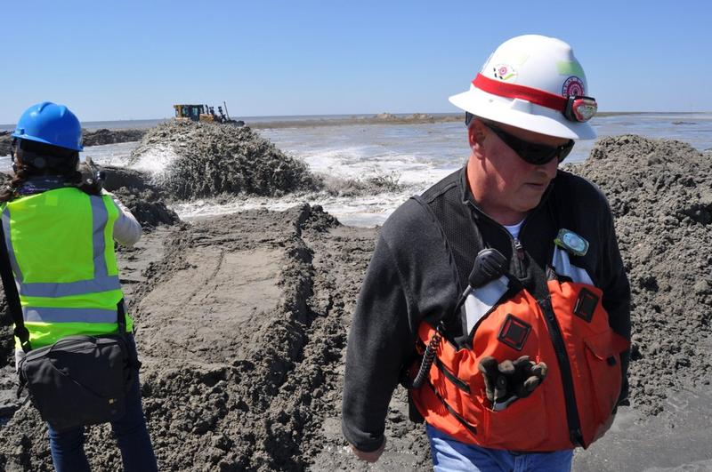 Workers watch as sediment dreged from the ocean is spewed out onto a beach during the rebuilding of Whiskey Island -- a barrier island along the Gulf of Mexico.