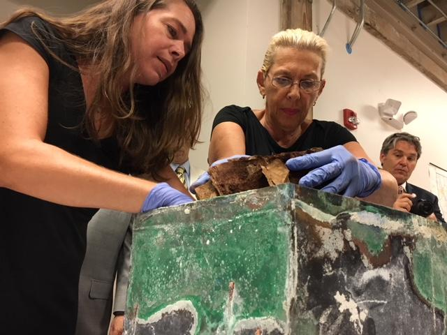 Restoration experts Beth Antoine and Jessica Hack remove the items, damaged by a water leak in the capsule.