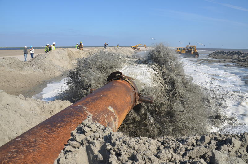 """Sediment pours out of a pipeline as part of Louisiana's Caminada Headland restoration project near Port Fourchon. A new federal bill will require the Corps to consider similar """"green"""" projects when building infrastructure."""