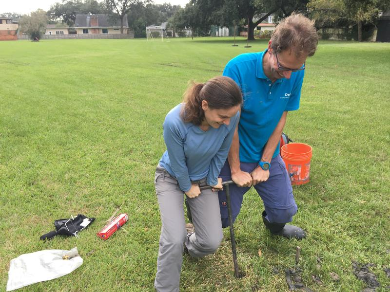 Molly Keogh, of Tulane University, and Marc Hijma, of Deltares, a Dutch research organization, turn a corkscrew-like auger deep into the ground to pull up a soil sample.