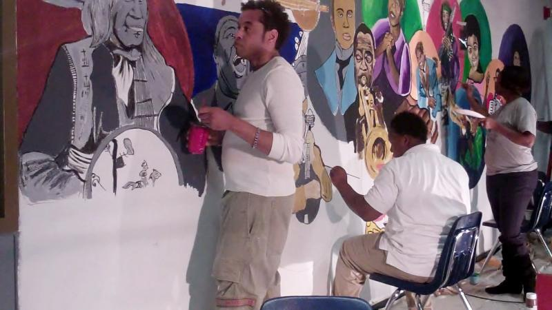 Artist Jamar Pierre (leftt) and students at West St. John High School work on a mural project.