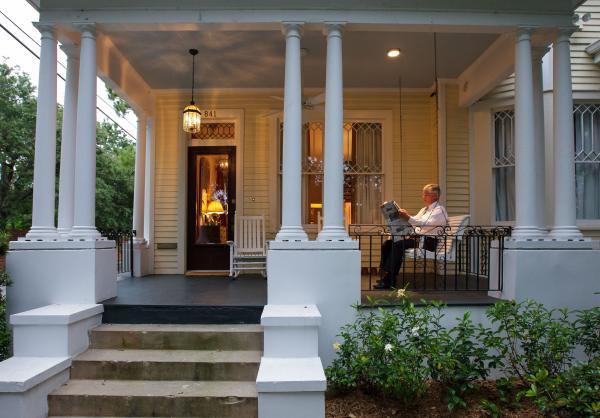 Michael Fitzpatrick reads on his porch on Audubon Park.
