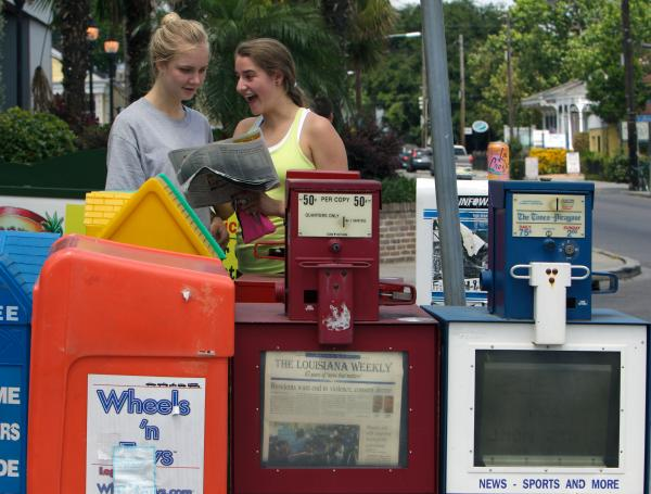 Jenny Kjellgerin (left) and Ava Ellison, graduating seniors at Ben Franklin High School, pick up a copy of The Advocate on Magazine Street. On a Tuesday morning it's the only local daily paper, and on this day Ava happened to appear on the front page. Former Times-Picayune photographer John McCusker, who now works for The Advocate, had taken her picture at a Planned Parenthood rally the day before.