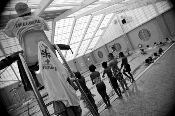 Kids wait to jump into the pool under the watchful eye of a NORDC lifeguard.