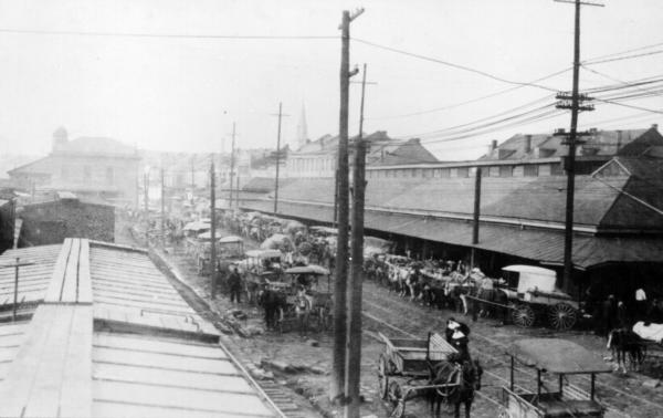 Horse-drawn wagons line the narrow street in front of New Orleans' French Market, Jan. 1915.